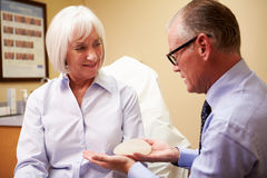 Woman Discussing Breast Augmentation With Plastic Surgeon. In Clinic Holding Silicon Breast stock image