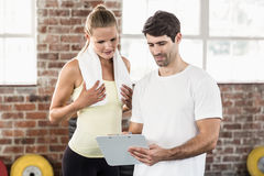 Woman discussing her performance on clipboard with trainer Stock Photos