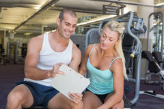 Woman discussing her performance on clipboard with trainer at gym Royalty Free Stock Images
