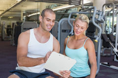 Woman discussing her performance on clipboard with a trainer at gym Stock Images