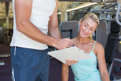 Woman discussing her performance on clipboard with a trainer at gym Stock Photography