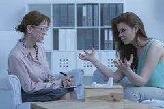 Woman discussing with psychologist Stock Photography