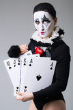 Woman in disguise harlequin. On a gray background stock photography