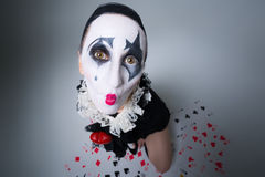 Woman in disguise harlequin. On a gray background stock image