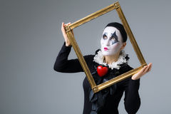 Woman in disguise harlequin. In the picture frame stock images