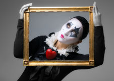 Woman in disguise harlequin. In the picture frame stock photos