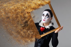 Woman in disguise harlequin in the picture frame. royalty free stock photos