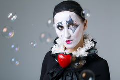 Woman in disguise harlequin. With soap bubbles in the background royalty free stock photos