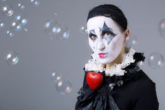 Woman in disguise harlequin. With soap bubbles in the background royalty free stock photo