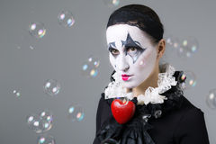 Woman in disguise harlequin. With soap bubbles in the background royalty free stock image