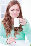 Woman disgusting smell of coffee with face expression royalty free stock photography