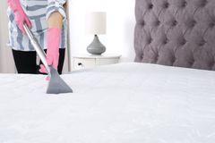 Woman disinfecting mattress with vacuum cleaner, closeup. Space for text royalty free stock photography