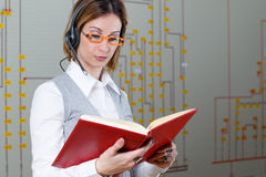 Woman dispatcher with hadphone reading a red book Stock Images