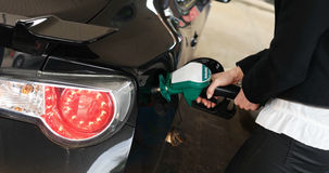 Woman dispensing fuel from a petrol pump Royalty Free Stock Photography