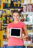 Woman Displaying Digital Tablet In Hardware Shop Stock Images