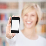 Woman Displaying Mobile Phone In Library. Closeup of woman displaying mobile phone in library Stock Photo