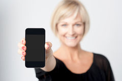 Woman displaying new phone in market Stock Photos