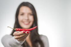 Woman displaying a red hot chilli pepper Stock Photos