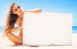 Woman displaying white placard for your text. Beautiful young woman on a beach holding a blank board for your text Royalty Free Stock Photo