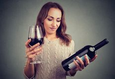 Woman displeased with wine taste. Young girl with bottle and glass of red wine looking grumpy because of bad taste stock image