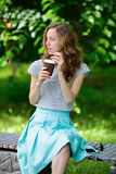 Woman with disposable coffee cup is sitting on a bench in the park Royalty Free Stock Photo
