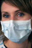 Woman with Disposable Face Mask. Woman with pretty blue eyes wearing a dental or medical technician's mask, close-up Royalty Free Stock Photo