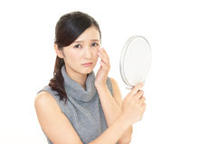 Woman dissatisfied with the skin care. Asian woman looking at her face in mirror Royalty Free Stock Image