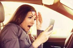 Woman distracted reading a message on cellphone, amazed, while driving a car stock image