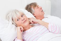 Woman disturbed with man snoring. Portrait Of Senior Angry Woman Awaken By Her Husband Snoring Stock Images