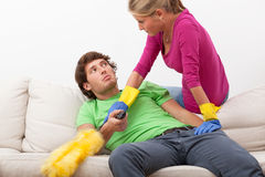 Woman disturbing her husband in watching tv. Woman with cleaning duster disturbing her husband in watching tv Stock Photography