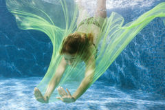 Woman dives with a fabric. Royalty Free Stock Photo