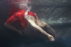 Woman dives underwater in a dress. Woman dives under the water in a dress, she is in the pool Stock Photos
