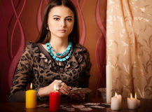 Woman with divination cards in room. Young woman with divination cards in room Royalty Free Stock Images