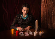 Woman with divination cards in room. Young woman with divination cards in room Royalty Free Stock Photos