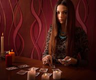 Woman with divination cards in room. Young woman with divination cards in room Royalty Free Stock Photography