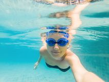 A woman with diving glasses is swimming in the pool under the water stock photography