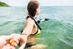 Woman with diving googles dragging partner to the sea Stock Photo