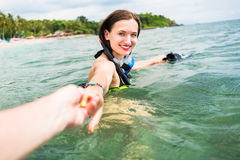 Woman with diving googles dragging partner to the sea. Woman wearing bikini and diving googles dragging her partner to the open sea, they have a vacation stock photography