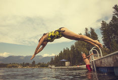 Woman diving off the dock of lake while on summer vacation Royalty Free Stock Image