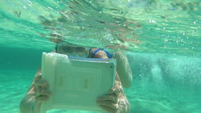 Woman diving with pad to make a good underwater. Slow motion of woman in snorkel diving in clear blue water with pad in water-proof case. She trying to make good stock video footage