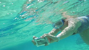 Woman diving with phone to make shot. Slow motion of a woman in snorkel diving with smart phone in water-proof case. Making selfie or taking pictures underwater stock video