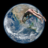 Woman diving on the planet earth. A woman in a bathing suit (bikini) is diving on the planet earth. Full view Stock Photos
