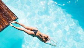 Woman diving in the pool. Overhead of woman diving in the pool royalty free stock photos