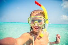 Woman diving in the sea. Young beautiful woman with snorkeling mask taking a selfie on a tropical beach - Attractive girl smiling while on a summer vacation Royalty Free Stock Photos