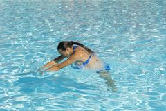 Woman diving in the swimming pool. Young beautiful girl swimming in pool. Brunette relaxing in clear warm water on sunny day. Top. View Close up Slow motion royalty free stock photography