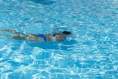 Woman diving in the swimming pool. Young beautiful girl swimming in pool. Brunette relaxing in clear warm water on sunny day. Top. View Close up Slow motion stock photography