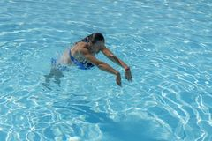 Woman diving in the swimming pool. Young beautiful girl swimming in pool. Brunette relaxing in clear warm water on sunny day. Top. View Close up Slow motion royalty free stock image