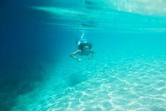 Woman diving swimming underwater view. Woman in sunglasses diving on a breath hold swimming under water view stock images