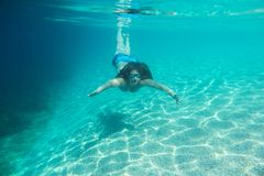 Woman diving swimming underwater view. Woman in sunglasses diving on a breath hold swimming under water view stock image