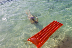 Woman diving under water towards a lilo stock photo